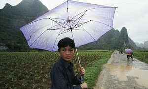 Student riding to school on rainy day in southwest China.