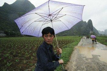 中国西南地区的学生在雨天里骑车上学。