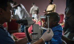 Mtoto manusura wa Ebola aitwaye Muhindo akichunguzwa macho  yake na Dkt. Steven Yeh