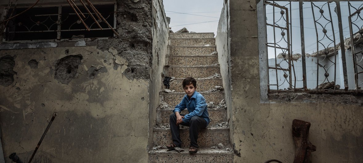 Mohammed, 10, sits on the staircase of the former house he used to hide with his family in Mosul.
