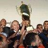 السفير الياباني تاكيشي أوكوبو، وممثل برنامج الأمم المتحدة الإنمائي يحملان كأس بطولة دوري طوكيو النهائية في غزة لتقديمه إلى فريق خان يونس الفائز بالبطولة.