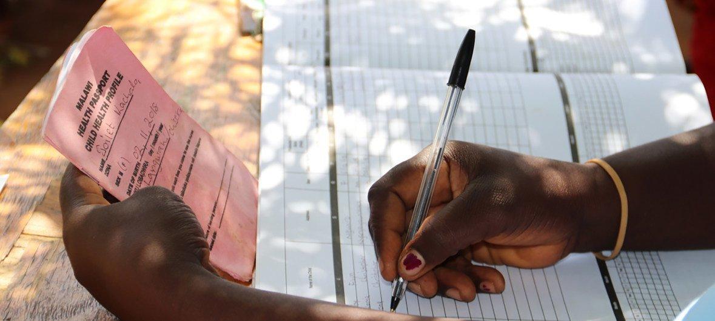 Una trabajadora de salud evalúa a los niños en Mkaka, Malawi, para determinar si son aptos para la vacuna contra la malaria.