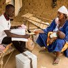 A mother in the remote village of Kombaka in Mali is handed a vaccination card after her child received an immunization administered by a health worker. (March 2019)