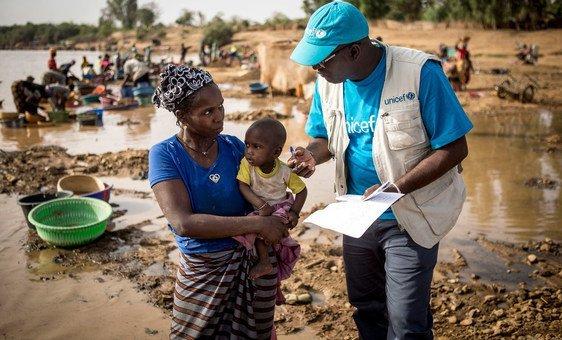 Un conseiller de l'UNICEF sur le terrain à Kayes, au Mali, explique à une mère à quel point il est important de vacciner son enfant. (Mars 2019)
