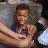 Un niño sonríe mientras recibe la vacuna contra el sarampión y la rubeola en Aden, Yemen, gracias a una campaña de UNICEF.