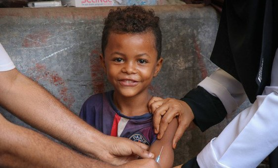 Criança sorri recebendo vácina contra o sarampo e rubéola no Iêmen