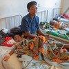 Una mujer cuida a su hijo que padece malaria en un hospital de Malawi.