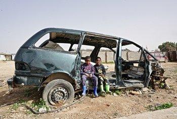 طفلان من النازحين داخليا يجلسان في إحدى السيارات المدمرة في مستوطنة قريونس للنازحين في بنغازي. ويعيش في هذه المستوطنة أكثر من  200 أسرة ، جميعهم تقريباً نزحوا من تاورغاء في عام 2011.