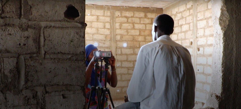 Mfanyakazi wa IOM akimpiga picha mhamiaji