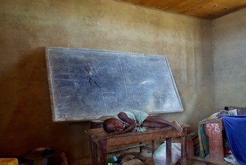 A child rests on a table in the classroom where her family is sleeping at a school used as a collective centre for internally displaced people in Oicha, Beni territory, North Kivu.