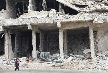 叙利亚阿勒颇,一名儿童走过遭到战火严重破坏的街道。