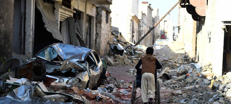 Un niño empuja una silla de ruedas en las calles del barrio de Al-Masjastiye, en el este de Aleppo.