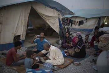 أسرة عراقية نازحة تتناول وجبة الإفطار في شهر رمضان، في مخيم للمشردين داخليا في كردستان العراق.