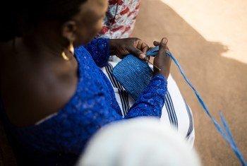 Au Burkina Faso, un membre du groupe NEERE tisse à la main un petit sac bleu en plastique dans le cadre d'une initiative visant à soutenir la création de revenus pour les femmes et les jeunes de ce pays d'Afrique de l'Ouest.
