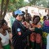 نادية خليفي، ظابطة حفظ سلام تونسية تعمل مع بعثة الأمم المتحدة في جمهورية أفريقيا الوسطى، تتحدث إلى نساء محليات أثناء دورية شرطية.