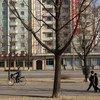 朝鲜儿童和成人经过首都平壤的一栋高层公寓楼。 2004年7月,城市住宅中的电力和水短缺十分普遍。
