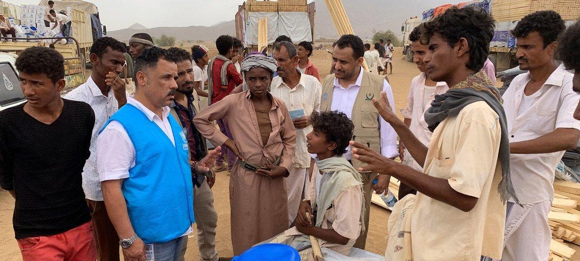 Un miembro de la Agencia para los refugiados habla con niños desplazados en Yemen.