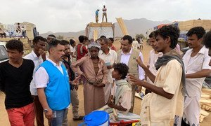 A UNHCR staff member talks to displaced children and others in Yemen's Hajjah Governorate. (21 March 2019)