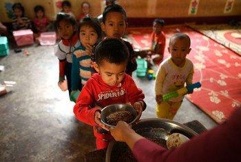 Niños en una escuela en el distrito de Xay, en la República Popular Democrática de Laos, reciben sus comidas.