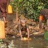 Crianças recolhem água de superfícia não tratada para consumo