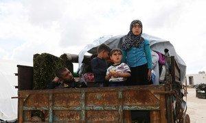 Una familia siria huye en la parte trasera de un cambio del conflicto en Kafr Lusein.