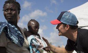 Em Moçambique,Orlando Bloom visita com Logina Jona, de 5 meses, e sua mãe, Sonia Paulo Jona, deslocadas pelo impacto dos recentes ciclones e agora vivendo no Local de Reassentamento Mutua.
