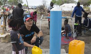 Orlando Bloom ajuda uma criança a encher um galão cheio de água da Unicef no local de reassentamento de Mendruzi para pessoas deslocadas pelos recentes ciclones.