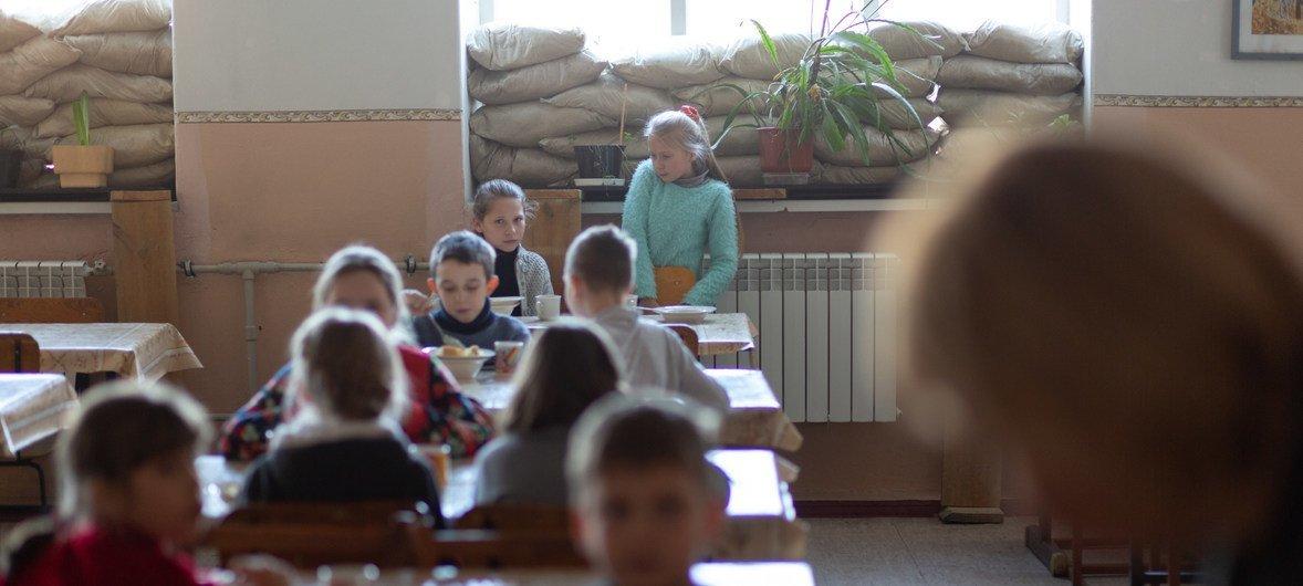 Дети на востоке Украины учатся в школах, стены которых повреждены снарядами, а окна заложены мешками с песком.