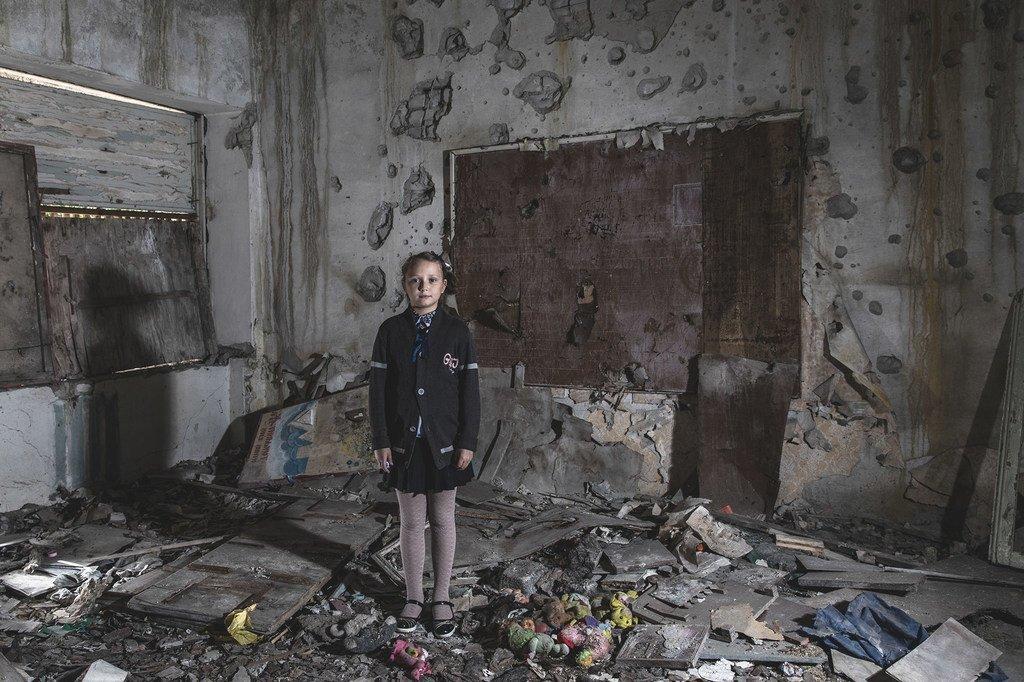Masha Khromchenko se tient debout dans une salle de classe de maternelle qui a été directement touchée par un obus dans la région de Louhansk, en Ukraine. (archive : 23 septembre 2018)