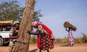 Mlinda amani mwanamke kutoka Ethiopia akimsaidia mwanamke Sudan Kusini kubeba kuni kichwani