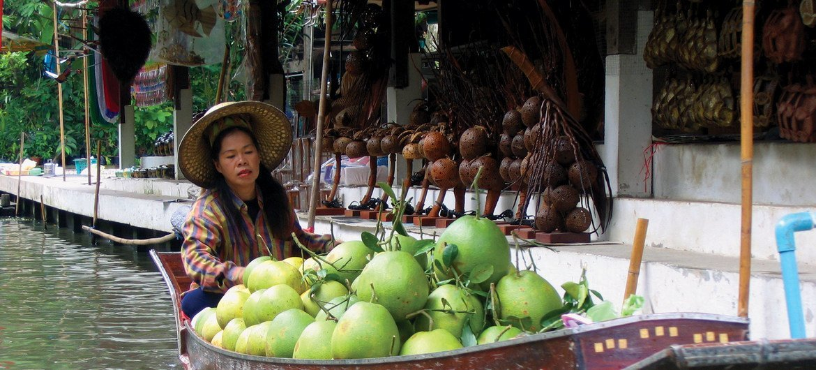 A saleswoman sells Asian grapefruits on a floating market.