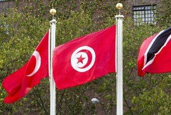 A bandeira da Tunísia (centro)  no mastro na sede das Nações Unidas em Nova Iorque.