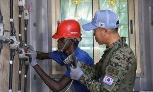 दक्षिण कोरियाई शांतिरक्षकों से इलैक्ट्रॉनिक्स इंजीनियरिंग में प्रशिक्षण प्राप्त करता एक युवक.