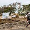 Una mujer pasea con su bebé en las afueras de Beira, Mozambique, en un reasentamiento para las personas desplazadas por los ciclones  Idai y Keith