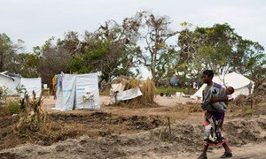 A woman carries her baby through a resettlement site for people displaced by cyclones outside Beira, Mozambique. (28 May 2019)
