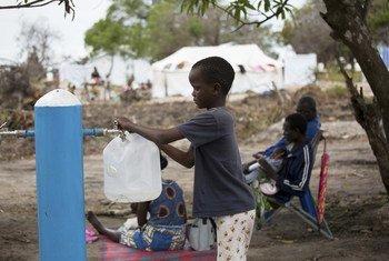 Un enfant rempli un bidon d'eau dans le camp pour personnes déplacées par les récents cyclones au Mozambique.