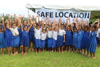 Children in a Samoan village gathered at a safe location during a disaster drill.
