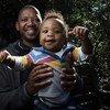 दक्षिण अफ्रीका के केपटाउन में एक पिता बोनगामी नकेम अपने आठ महीने के बच्चे - खूमा के साथ