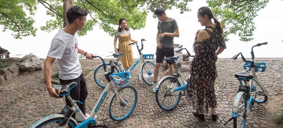 Youth riding share bikes and hanging out by the UNESCO World Heritage Site West Lake in Hangzhou, China.