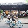 年轻人骑车经过中国杭州的西湖,西湖被列入教科文组织世界遗产名录。