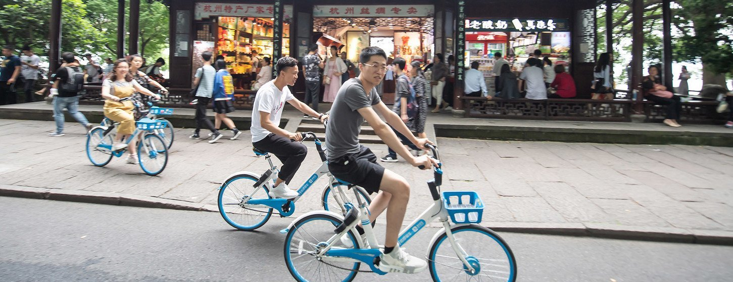Youth riding share bikes along the UNESCO World Heritage Site West Lake in Hangzhou, China.