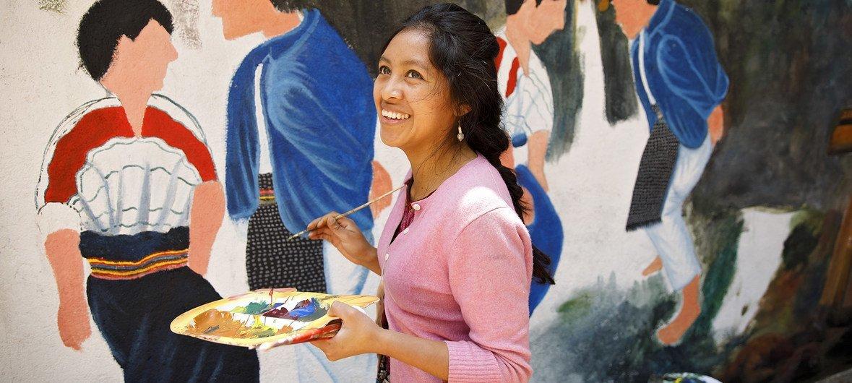 """Una artista local pinta el Centro para la Memoria Histórica de las Mujeres"""" en San Juan Comalapa, en Guatemala."""