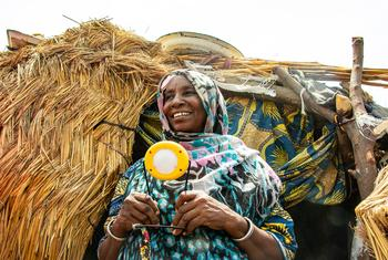 Hauwa's GOGLA lamp helps her cook and carry out other chores around her home, and it helps her children study.