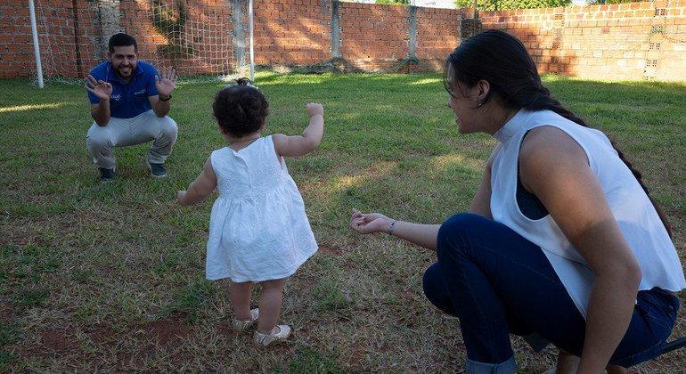 Paula de un año de edad, juega con sus padres.