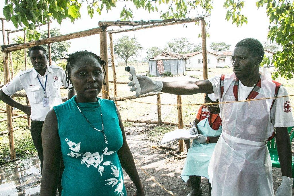 Un volontaire de la Croix-Rouge en Ouganda prend la température d'une femme en provenance de République démocratique du Congo pour détecter les symptômes d'Ebola (février 2019).