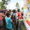 Mfanyakazi wa kujitolea katika shirika la msalaba mwekundu nchini Uganda akielimish watu kuhusu hatari za Ebola kupitia bango lililoandaliwa na shirika la Umoja wa Mataifa la kuhudumia watoto, UNICEF. Mafunzo hayo kwa watu wanaovuka mpaka kutoka DRC.