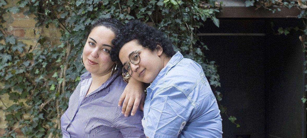 """同为23岁的米拉尔(左)和诺兰为了逃避迫害,从祖国埃及来到了加拿大。在发现女儿是女同性恋后,米拉尔的父亲要求她进行""""贞洁测试"""",甚至威胁会要她的命。而诺兰的家人则对她实施殴打,还把她关进了精神病院。她们的照片在由难民署支持的题为""""爱一个人我错了吗""""摄影中展出,该摄影展共包含了12个国家、20位性少数难民的肖像。"""