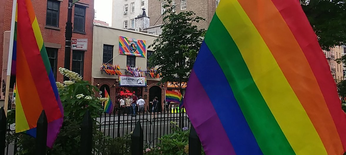 The Stonewall Inn, site of the 1969 riots that launched the gay rights movement, photographed between two Rainbow Flags in Greenwich Village, New York City.