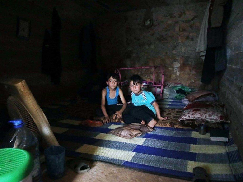叙土边境地区,两名逃离伊德利卜战火的叙利亚男童正在一处临时住所内吃饭。