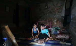Having fled hostilities in Syria's Idlib, two boys have a meal in their temporary shelter, near the Turkish border.  (June 2019)